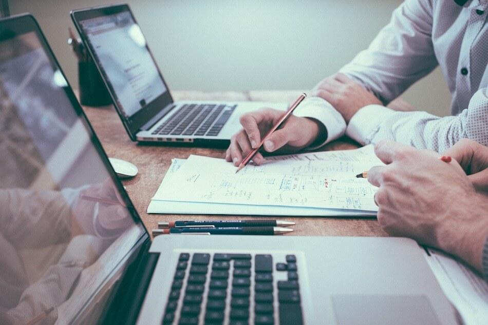 Dva muškarca sa računalima, papirima i olovkama rade na izradi financijskog plana